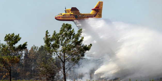 A Canadair plane drops water on a forest fire in Lacanau, southwestern France, Friday, Aug. 17, 2012. French firefighters fought a wildfire on Friday that has destroyed a large swathe of forest and scrubland near a popular seaside and surfing resort in southwestern France. (AP Photo/Bob Edme)