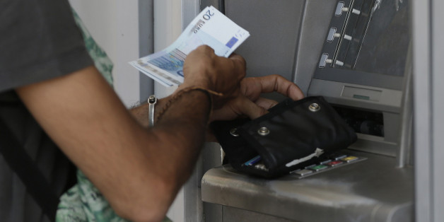 A man uses an ATM of a bank after the government's decision last week to limit daily cash withdrawals to 60 euro ($66) in Athens, Tuesday, July 7, 2015. Greek Prime Minister Alexis Tsipras was heading Tuesday to Brussels for an emergency meeting of eurozone leaders, where he will try to use a resounding referendum victory to eke out concessions from European creditors over a bailout for the crisis-ridden country. (AP Photo/Petr David Josek)