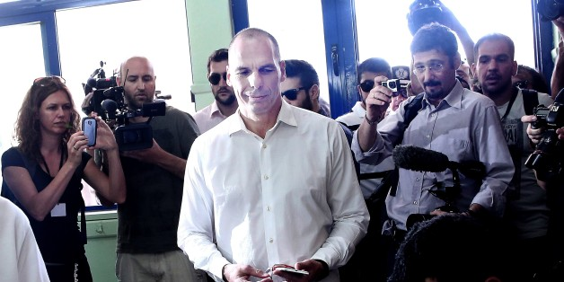 Greek Finance Minister Yanis Varoufakis (C) prepares to cast his ballot during the Greek referendum on its bailout terms in Athens on July 5, 2015. Greece voted in a tightly fought referendum on July 5 that Prime Minister Alexis Tsipras said will determine its 'destiny' in the eurozone, as the EU country teetered on the brink of financial collapse.   AFP PHOTO / ANGELOS TZORTZINIS        (Photo credit should read ANGELOS TZORTZINIS/AFP/Getty Images)