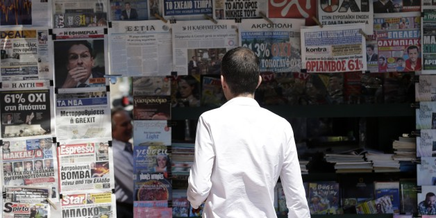 A man reads the front pages of the Greek newspapers in Athens, Monday, July 6, 2015. Greek Finance Minister Yanis Varoufakis resigned Monday, saying he was told shortly after Greece's decisive referendum result that some other eurozone finance ministers and the country's other creditors would appreciate his not attending the ministers' meetings. (AP Photo/Petr David Josek)