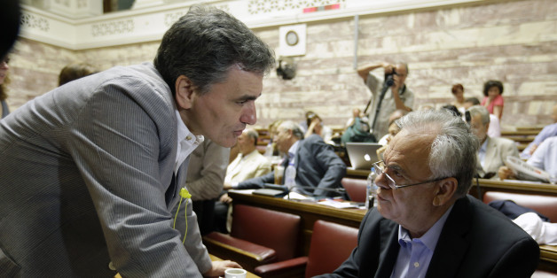 Greek Finance Minister Euclid Tsakalotos, left, speaks with Deputy Prime Minister Giannis Dragasakis before a meeting with lawmakers of Syriza party at the Greek Parliament in Athens, Friday, July 10, 2015. Greece's Prime Minister Alexis Tsipras will seek backing for a harsh new austerity package from his party Friday to keep his country in the euro — less than a week after urging Greeks to reject milder cuts in a referendum. (AP Photo/Thanassis Stavrakis)