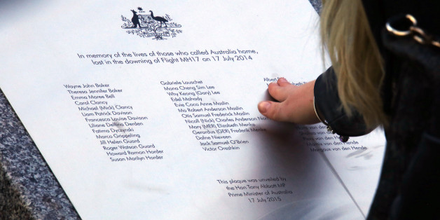 CANBERRA, AUSTRALIA - JULY 17:  A relative of an Australian victim of Malaysia Airlines jet MH17 touches a memorial that was unveiled outside Parliament House on July 17, 2015 in Canberra, Australia. 298 people died when Malaysian Airlines flight MH17 was struck down by a missile over Ukraine on 17 July, 2014.  (Photo by David Gray- Pool/Getty Images)
