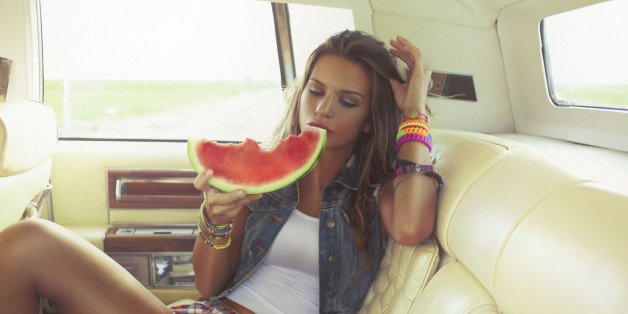 Beautiful young hipster woman eating piece of juicy watermelon on the back seat of the car. Shallow DOF; Soft focused; developed from RAW; retouched with special care and attention; small amount of grain added for best final impression; ready made for print and web use;