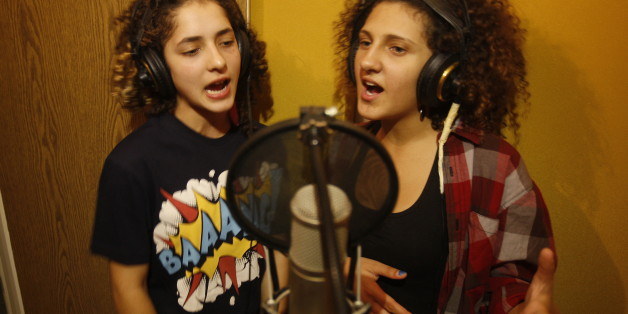 TO GO WITH AFP STORY LIFESTYLE-ISRAEL-PALESTINIAN-ARAB-ENTERTAINMENT-MUSICArab Israeli youths Amani Tatour (R) and Mai Dmar(L) sing the rap duo 'Damar' (Arabic for destruction) in a studio in the city of Nazareth, northern Israel, on October 27, 2011.   Mai and Amane, Arab Israeli teenagers living in Nazareth, are happy to leave talk about boys and make-up to their peers. They have a political message and they're telling it through rap music. AFP PHOTO/AHMAD GHARABLI (Photo credit should read AH