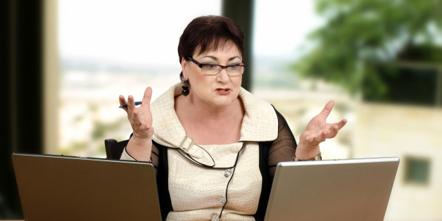Angry glasses teacher yelling at her student during online lesson. Mature brown haired woman is looking at leptop monitor and shakes her hands