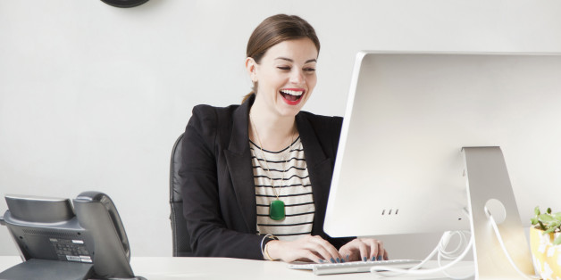 Studio shot of young woman working on computer and laughing