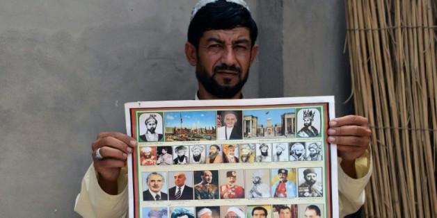 Un afghan montre un calendrier ou figurent les photographies des leaders afghans, y compris le dernier chef des talibans le mollah Omar, à Kandahar le 31 juillet 2015
