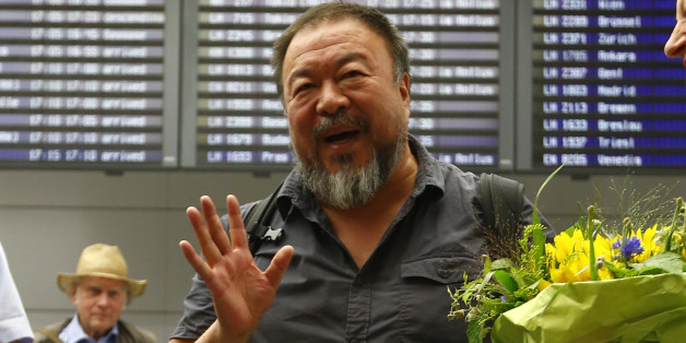 Chinese dissident artist Ai Weiwei answers to questions of journalists after his arrival at the airport in Munich, Germany, Thursday, July 30, 2015. Ai Weiwei is on his way to Berlin where part of his family lives. Standing at right is Bavarian Green politician Margarethe Bause. (AP Photo/Matthias Schrader)