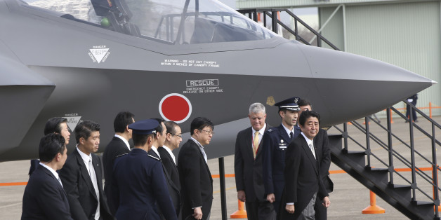 FILE - In this Oct. 26, 2014 file photo, Japanese Prime Minister Shinzo Abe, right, walks by a mock-up of the F-35 fighter jet during the annual Self-Defense Forces Commencement of Air Review at Hyakuri Air Base, north of Tokyo. Japan emphasized China as a threat in escalating regional tensions in this year's annual defense report, approved Tuesday, July 21, 2015 by the Cabinet, as Abe's government tries to convince the public of the need to pass legislation to give Japan's military a greater ro