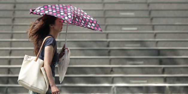 A woman uses an umbrella to shelter from the sun in Tokyo, Japan, on Monday, July 13, 2015. The Japan Meteorological Agency reported that Tokyo area recorded a temperature of 33.6 degrees on July 13. Photographer: Kiyoshi Ota/Bloomberg via Getty Images