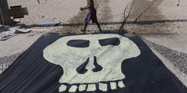 A man walks past a banner with a drawing of a skull symbolizing the death of nature during a protest on the Copacabana beach in Rio de Janeiro, Brazil, Saturday, Aug. 1, 2015. Less than a dozen people showed up for a scheduled protest by environmentalists against the money spent in preparation for the Olympics and the construction of the game's golf course that was partially carved out of a nature reserve. (AP Photo/Silvia Izquierdo)