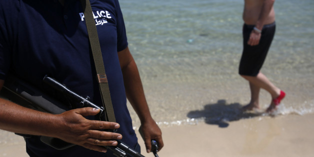 A Tunisian police officer guards the beach in front of the Imperial Marhaba Hotel in Sousse, Tunisia, Sunday, June 28, 2015. Tunisia's top security official says 1,000 extra police are being deployed at tourist sites and beaches in the North African nation. (AP Photo/Darko Vojinovic)