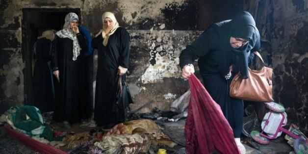 Des palestiniennes évaluent les dégâts dans la maison du bébé palestinien mort dans un incendie imputé à d
