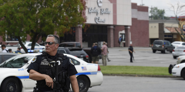An officer stands in front of the Carmike Hickory 8 movie theater following a shooting Wednesday, Aug. 5, 2015, in Antioch, Tenn. A suspect wielding a hatchet and a gun inside the Nashville-area movie theater died after exchanging gunshots with a SWAT team that stormed the theater, police said. (AP Photo/Mark Zaleski)