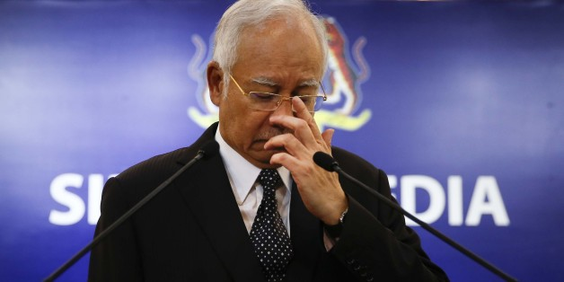 Malaysian Prime Minister Najib Razak, center, gestures before speaking at a special press conference announcing the findings for the ill fated flight MH370 in Kuala Lumpur, Malaysia, early Thursday, Aug. 6, 2015. Experts have confirmed that the debris found on Reunion Island last week was that of Malaysian Airlines flight 370 that went missing last year, Malaysia's prime minister said early Thursday. (AP Photo/Vincent Thian)