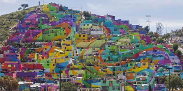 In this Thursday, July 30, 2015 photo, hundreds of houses painted in bright colors in what organizers claim is Mexico's largest mural, is part of a government-sponsored project is called Pachuca Paints Itself, in the Palmitas neighborhood, in Pachuca, Mexico. German Crew is the artist collective responsible for painting the mural project. Director Enrique Gomez, who goes by MYBE, said the crew has painted 1,500 square meters with 20,000 liters of paint. The project aims to bring the community together and rehabilitate the area. (AP Photo/Sofia Jaramillo)