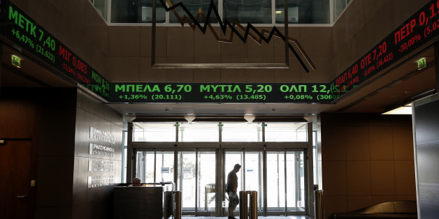 A man walks at the reception hall of the Athens' Stock Exchange as stock prices are on display on a ticker screen in Athens, Greece, on Tuesday, Aug. 4, 2015. The Stock Exchange is suffering a second day of losses after reopening amid capital controls, with banks again suffering the worst damage. (AP Photo/Yorgos Karahalis)