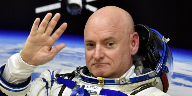 US astronaut Scott Kelly waves as his space suit is tested at the Russian-leased Baikonur cosmodrome, prior to blasting off to the International Space Station (ISS), late on March 27, 2015. The international crew of US astronaut Scott Kelly and Russian cosmonauts Gennady Padalka and Mikhail Kornienko is scheduled to blast off to the ISS from Baikonur early on March 28. AFP PHOTO / KIRILL KUDRYAVTSEV        (Photo credit should read KIRILL KUDRYAVTSEV/AFP/Getty Images)