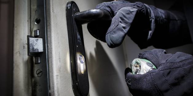 BERLIN, GERMANY - JUNE 27:  Posed scene of a man opening a door with gloves and flashlight  on June 27, 2014, in Berlin, Germany. The photo symbolizes the increasing risk of burglary in Germany. (Photo by Thomas Trutschel/Photothek via Getty Images)