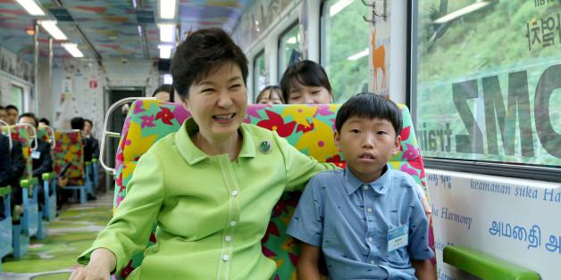 박근혜 대통령이 5일 강원도 철원군 백마고지역으로 가는 경원선 열차에서 탈북자 자녀 이정민군과 함께 앉아 있다.