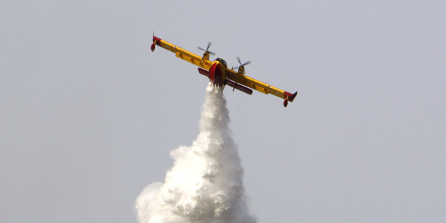 A Canadair plane helps to battle a forest fire near the village of Panaktos, some 40 kilometers (25 miles) northwest of Athens on Tuesday, July 15, 2008. Firefighters battled to stop a forest fire reaching a munitions factory authorities said. The Fire Service said at least one home was destroyed in the blaze and several others were damaged.(AP Photo/Thanassis Stavrakis)