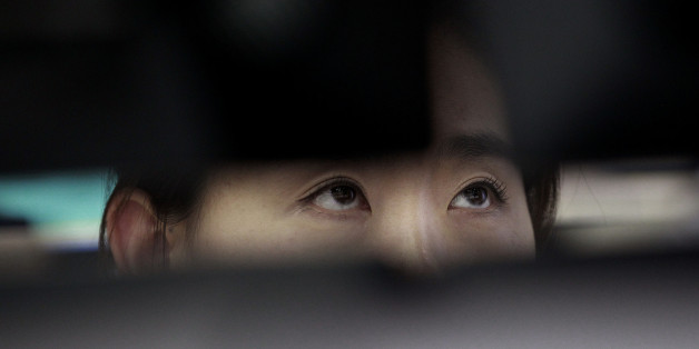 A currency trader watches monitors at the foreign exchange dealing room of the Korea Exchange Bank headquarters in Seoul, South Korea, Friday, July 11, 2014. Asian stock markets were muted Friday, following the lead of Wall Street traders spooked by worries about the soundness of a bank in Portugal that raised the specter of more financial turmoil in Europe. South Korea's benchmark Kospi dropped 0.70 percent at 1,988.74.( AP Photo/Ahn Young-joon).