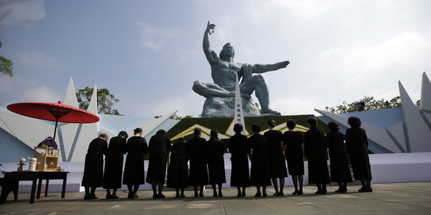 Visitor bow in front of the Peace Statue at the 70th anniversary of the atomic bombing in Nagasaki, southern Japan Sunday, Aug. 9, 2015. (AP Photo/Eugene Hoshiko)