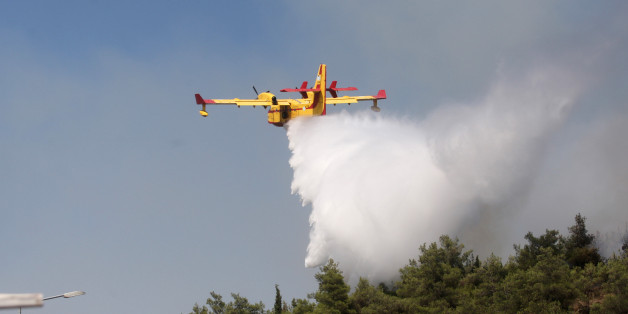 A Canadair drops water on a forest fire at the Thessaloniki Seih Sou park, which overlooks the city of Thessaloniki, on July 14, 2012. The risk of new fires was considered high, after several days of hot temperatures accross most of Greece. AFP PHOTO /SAKIS MITROLIDIS        (Photo credit should read SAKIS MITROLIDIS/AFP/GettyImages)