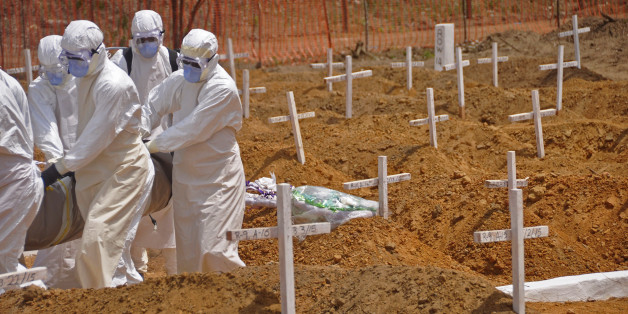 Health workers carry the body, of a person that they suspected died from the Ebola virus at a new graveyard on the outskirts of Monrovia, Liberia, Wednesday, March 11, 2015. Liberians held a church service Wednesday for families who lost members to Ebola to mark the country's 99th celebration National Decoration Day, a holiday normally set aside for people to clean up and re-decorate the graves of their lost relatives. (AP Photo/Abbas Dulleh)