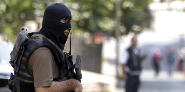A masked Turkish police officer secures a road leading to the U. S. Consulate building in Istanbul, Monday, Aug. 10, 2015. Two assailants opened fire at the building on Monday, touching off a gunfight with police before fleeing the scene, Turkish media reports said. (AP Photo/Lefteris Pitarakis)