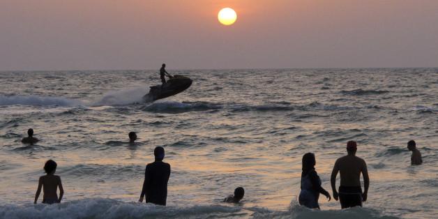 People enjoy a sunset swim at a public beach in Dubai, United Arab Emirates, Thursday, Sept. 6, 2012. (AP Photo/Hassan Ammar)