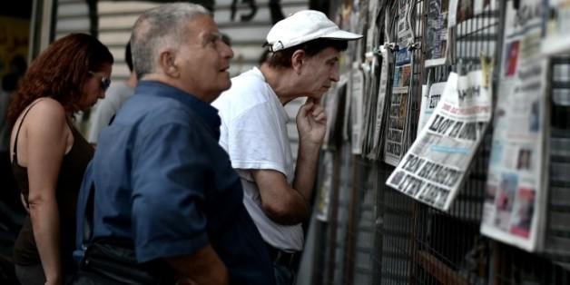 Des Grecs lisent les journaux du jour dans le centre d'Athènes, le 31 juillet 2015