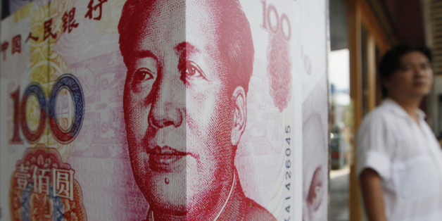 A man stands next to a copy of the Chinese RMB at a money exchange store in Hong Kong Friday, July 20, 2012. (AP Photo/Kin Cheung)
