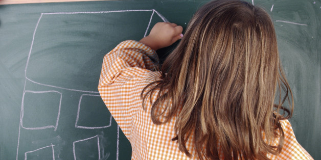 A left-handed girl drawing a house on a blackboard.Elementary and Primary School: Education