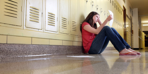 A middle school girl sitting in hallway of school looks upset while looking at her classwork.