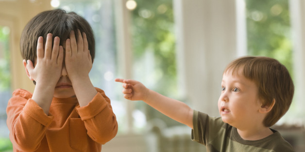 Boy pointing at brother who's covering his eyes