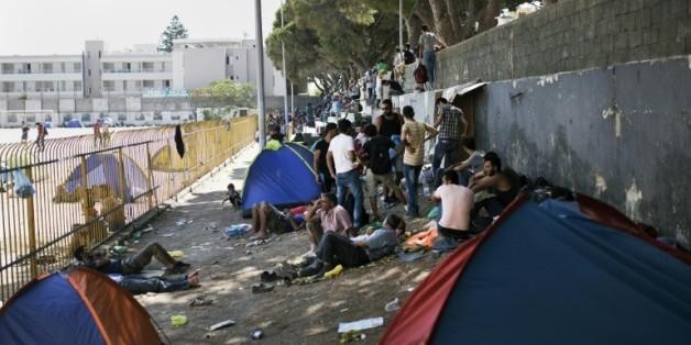 Des migrants attendent à l'extérieur du stade de l'île de Kos avant de pouvoir se faire enregistrer administrativement en Grèce, le 12 août 2015