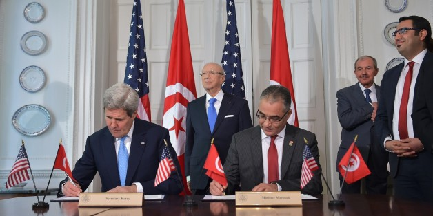 US Secretary of State John Kerry (L) and Tunisian Minister of Political Affairs Mohsen Marzouk (R) sign an memorandum of understanding watched by Tunisian President Beji Caid Essebsi (C) at Blair House, the presidential guest house, on May 20, 2015 in Washington, DC. AFP PHOTO/MANDEL NGAN        (Photo credit should read MANDEL NGAN/AFP/Getty Images)