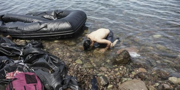 Un syrien embrasse la terre à son arrivée sur l'île grecque de Lesbos, le 14 août 2015 après avoir traversé la mer Egée en partant de Turquie