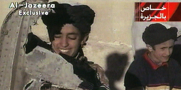 """In this image made from video broadcast by the Qatari-based satellite television station Al-Jazeera Wednesday, Nov. 7, 2001, a young boy, left, identified as Hamza bin Laden holds what the Taliban says is a piece of U.S. helicopter wreckage in Ghazni, Afghanistan on Monday, Nov. 5, 2001. The Qatar based broadcaster identified the boy as one of the sons of Osama bin Laden, the prime suspect in the Sept. 11, attacks on the United States. Boy at right is unidentified. Graphic at top right reads """"Ex"""