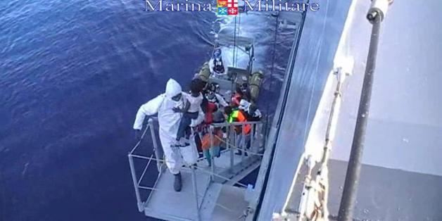 This image taken from video provided by the Italian Navy (Marina Militare) Saturday, Aug. 15, 2015, shows migrants boarding a navy vessel after being rescued from a fishing boat, off the coast of Libya. At least 40 migrants died on Saturday in the hold of an overcrowded smuggling boat in the Mediterranean Sea north of Libya, apparently killed by fuel fumes. Some 320 others on the same boat were saved by the Italian navy, the rescue ship's commander said. Migrants by the tens of thousands are bra