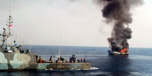 Smoke billows from M.V. Karunia Laut-1, left, as it caught on fire after being shot by an Indonesian Navy patrol boat off Surabaya, East Java, Tuesday, Nov. 11, 2003. The M.V. Karunia Laut-1 was destroyed after the Thai crew on board was arrested for illegal fish poaching in the waters north of Bawean island in eastern Indonesia on Sunday. Illegal fishing costs Indonesia about $3 billion a year. (AP Photo/Trisnadi)