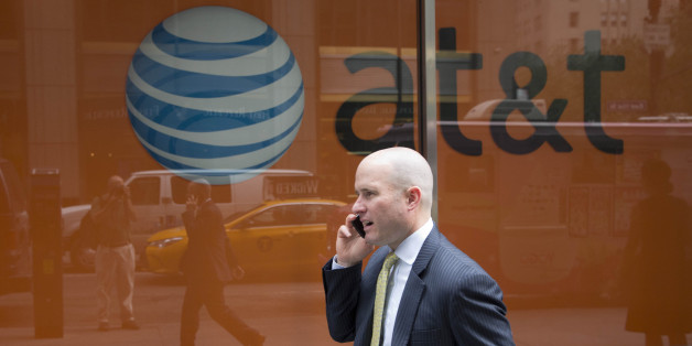 A man using a mobile phone walks past an AT&T store, Tuesday, June 23, 2015 in New York. (AP Photo/Mark Lennihan)