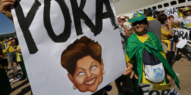 """A demonstrator shows a poster that reads in Portuguese """"Out"""" with the image of Brazil's President Dilma Rousseff, during a  protest against the government of Brazil's President Dilma Rousseff, in front of the Brazilian National Congress, in Brasilia, Brazil, Sunday, Aug. 16, 2015. Demonstrators are taking to the streets across Brazil for a day of nationwide anti-government protests. President Rousseff's second term in office has been shaken by a snowballing corruption scandal involving politicia"""