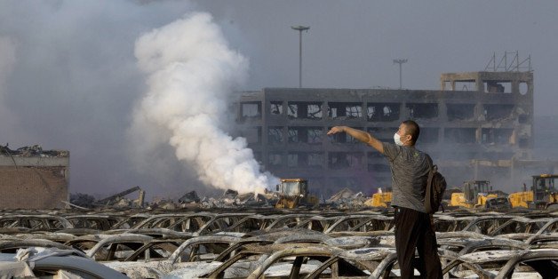 In this photo taken Thursday, Aug. 13, 2015, a man walks through the site of an explosion at a warehouse in northeastern China's Tianjin municipality. Rescuers have pulled a survivor from an industrial zone about 32 hours after it was devastated by huge blasts in China's Tianjin port. Meanwhile, authorities are moving gingerly forward in dealing with a fire still smoldering amid potentially dangerous chemicals. (AP Photo/Ng Han Guan)