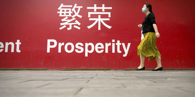 "A woman walks past a banner reading ""Prosperity"" in English and Chinese on a street in central Beijing, Wednesday, July 15, 2015. China's economic growth in the latest quarter held steady at 7 percent, its weakest performance since the global crisis, but better retail sales and factory output in June suggested efforts to reverse the slump might be gaining traction. (AP Photo/Mark Schiefelbein)"