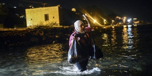 Une migrante marche vers un bateau pour embarquer de Bodrum, ville touristique sur la côte égéenne en Turquie, pour l'île de Kos en Grèce, le 18 août 2015
