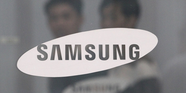 Employees walk past a logo of Samsung Group at the head office of Samsung C&T Corp. in Seoul, South Korea, Friday, July 17, 2015. Samsung shareholders approved Friday a highly contested deal that strengthens the Samsung family's grip on the world's largest smartphone maker. Samsung construction company Samsung C&T said that 69.5 percent of shareholders who voted supported the takeover of it by another Samsung company, Cheil Industries. (AP Photo/Ahn Young-joon)