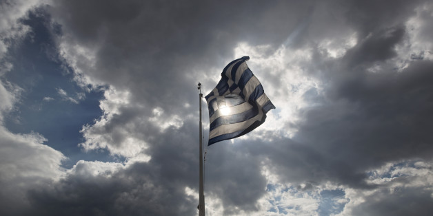 Tourists stand beneath a Greek flag fluttering against  the sun at the ancient Acropolis hill , in Athens, on Monday June 22, 2015. A top European Union official said that debt talks between Greece and its international creditors have made some progress but that a deal to avoid potential bankruptcy remains elusive. (AP Photo/Petros Giannakouris)
