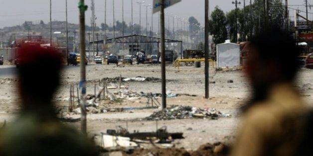 Des peshmergas kurdes regardent un checkpoint tenu par les combattants du groupe Etat islamique le 16 juin 2015 à l'entrée de la ville de Mossoul